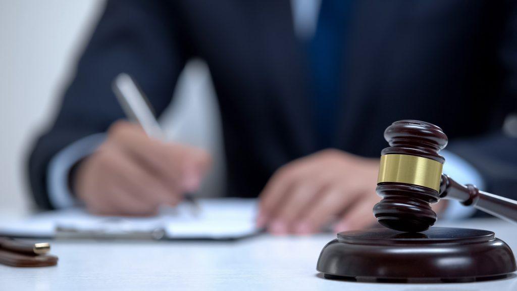 Judge writing on clipboard.